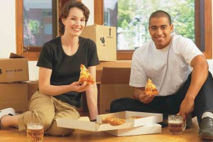 photo: new home buyer young couple sitting on floor eating pizza